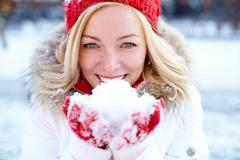 Portrait of happy girl holding snow on palms and looking at camera Stock Photos