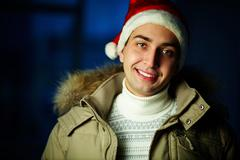 portrait of young man in santa cap looking at camera with smile - stock photo