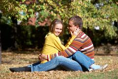 Photo of happy girl with handsome male sitting on ground in autumn Stock Photos