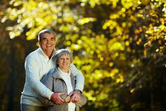 Photo of senior couple spending free time in autumn forest Stock Photos