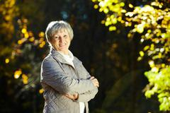 photo of senior woman in the park in autumn - stock photo