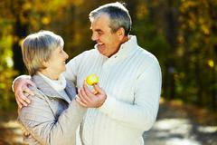 Photo of amorous aged man and woman holding apple and looking at each other Stock Photos