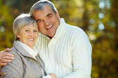 photo of amorous aged man and woman looking at camera - stock photo