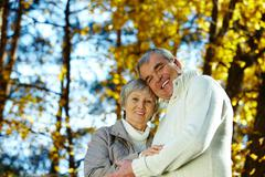 Photo of amorous aged man and woman looking at camera in autumnal park Stock Photos
