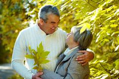Stock Photo of photo of amorous aged man and woman looking at each other in autumnal park