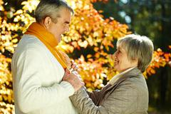 Photo of amorous aged man and woman looking at each other in autumnal park Stock Photos