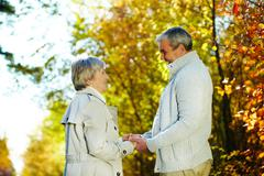 photo of senior couple looking at each other in the park - stock photo
