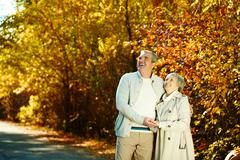 Stock Photo of photo of happy aged man and woman looking at something in autumnal park