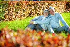 photo of happy aged man and woman looking at camera in autumnal park - stock photo