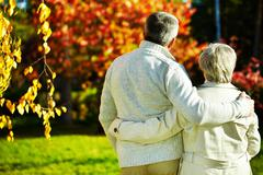 Rear view of aged man and woman taking a walk in autumnal park Stock Photos