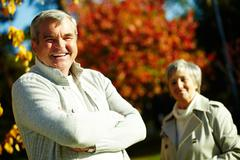 Photo of happy aged man looking at camera with his wife on background Stock Photos