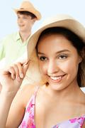 portrait of happy girl in hat looking at camera with man on background - stock photo
