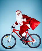 photo of happy santa claus with red sack riding bike - stock photo