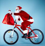 photo of happy santa claus on bike with red sack in stretched arm - stock photo