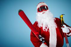 photo of happy santa claus with skis looking at camera - stock photo