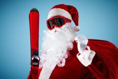 photo of happy santa claus with skis and sack looking at camera - stock photo