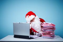 portrait of santa claus touching head while looking at heap of letters in front - stock photo
