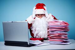 Portrait of terrified santa claus touching head in front of laptop and heap of l Stock Photos