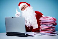 Portrait of santa claus sitting with raised forefinger in front of laptop and he Stock Photos