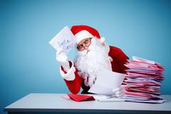 Portrait of santa claus thinking about ideas while reading letters Stock Photos