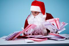 portrait of confused santa claus holding letters and looking at them in trouble - stock photo
