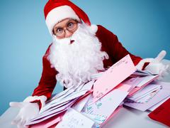 Portrait of astonished santa claus holding letters and looking at them in troubl Stock Photos