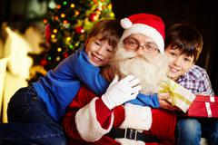 Photo of happy boy embracing santa claus with cute kid near by Stock Photos