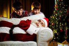 photo of santa claus sleeping on sofa with two happy boys looking at him - stock photo