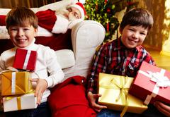 photo of happy boys holding gifts with santa claus sleeping on sofa on backgroun - stock photo
