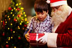 Photo of cute boy and santa claus holding giftbox and looking at it Stock Photos