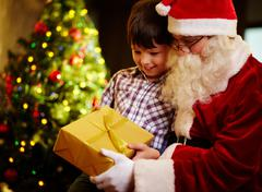 photo of cute boy and santa claus holding giftbox and looking at it - stock photo