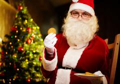 Photo of happy santa claus in eyeglasses looking at camera while holding biscuit Stock Photos