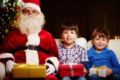 photo of cute boys and santa claus holding giftboxes and looking at camera - stock photo