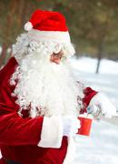 santa claus drinking hot tea in winter forest - stock photo