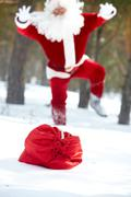 santa claus running to his sack lost in winter wood - stock photo