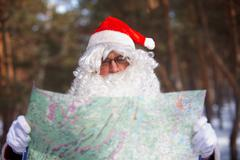santa claus looking at map in wood - stock photo