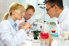 Group of clinicians experimenting with new substance in laboratory Stock Photos