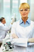 portrait of a pretty scientist looking at camera against her working colleague - stock photo
