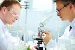 portrait of two male chemists researching in laboratory - stock photo