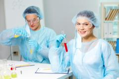 confident clinician studying new substance in laboratory with her colleague on b - stock photo