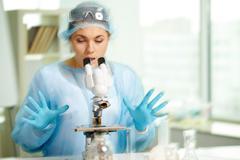 Yllättynyt kliinikon etsii mikroskoopilla laboratoriossa Kuvituskuvat