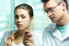 serious scientist explaining chemical formula to his co-worker - stock photo