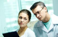 serious chemists looking at formula on transparent board - stock photo