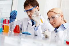 serious clinicians looking at flasks with liquid in laboratory - stock photo