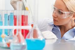 serious clinician looking at flask with liquid in laboratory - stock photo