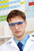 serious chemist looking at camera in laboratory - stock photo
