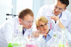 Creating medicine three chemists researching liquid in tubing Stock Photos