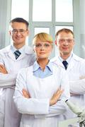 Medical team portrait of three doctors looking at camera and smiling Stock Photos