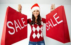 Happy girl in santa cap holds red paperbags with symbol of sale Stock Photos