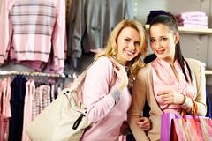 image of two pretty girls looking at camera with smiles in department store - stock photo